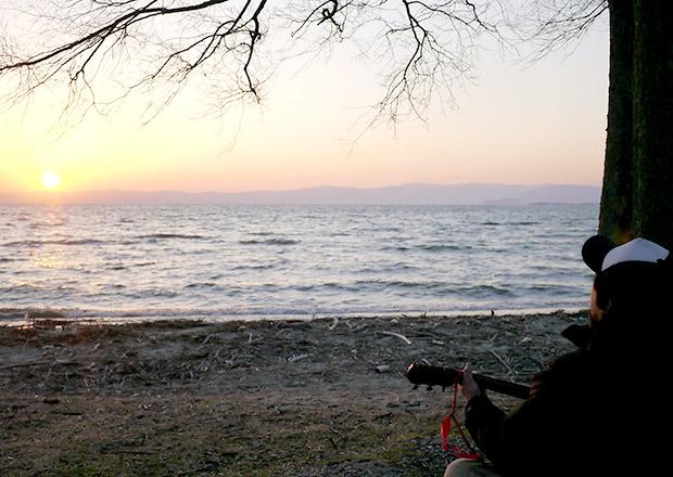 琵琶湖で夕日を見ながらギターを弾く