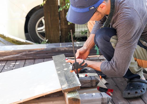 ビスやクリップ等でベニア板を固定している様子