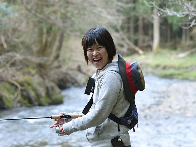 笑顔で渓流釣りをする人