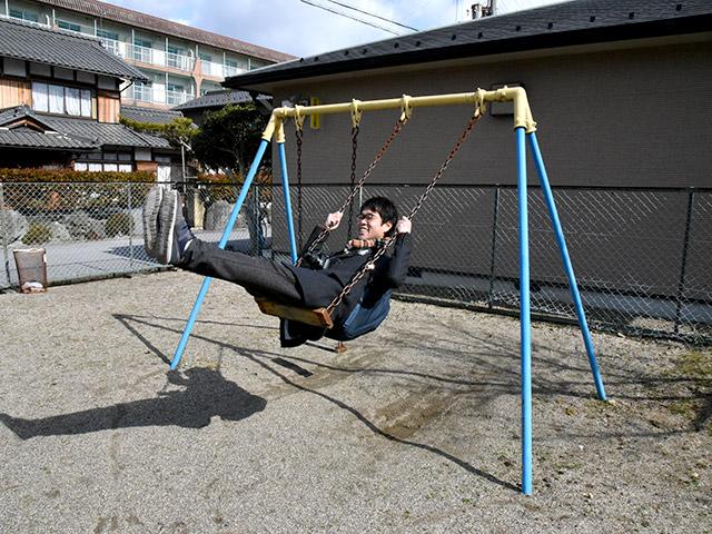 公園のブランコで遊ぶ大人